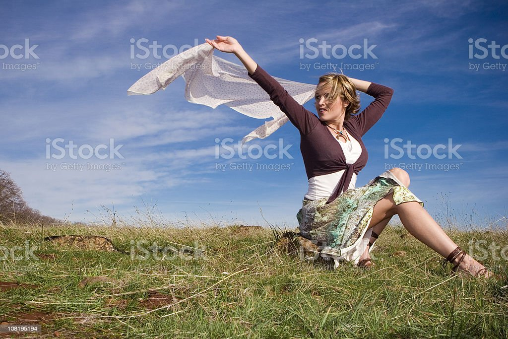 Young Woman Sitting in Field and Holding Scarf to Wind royalty-free stock photo