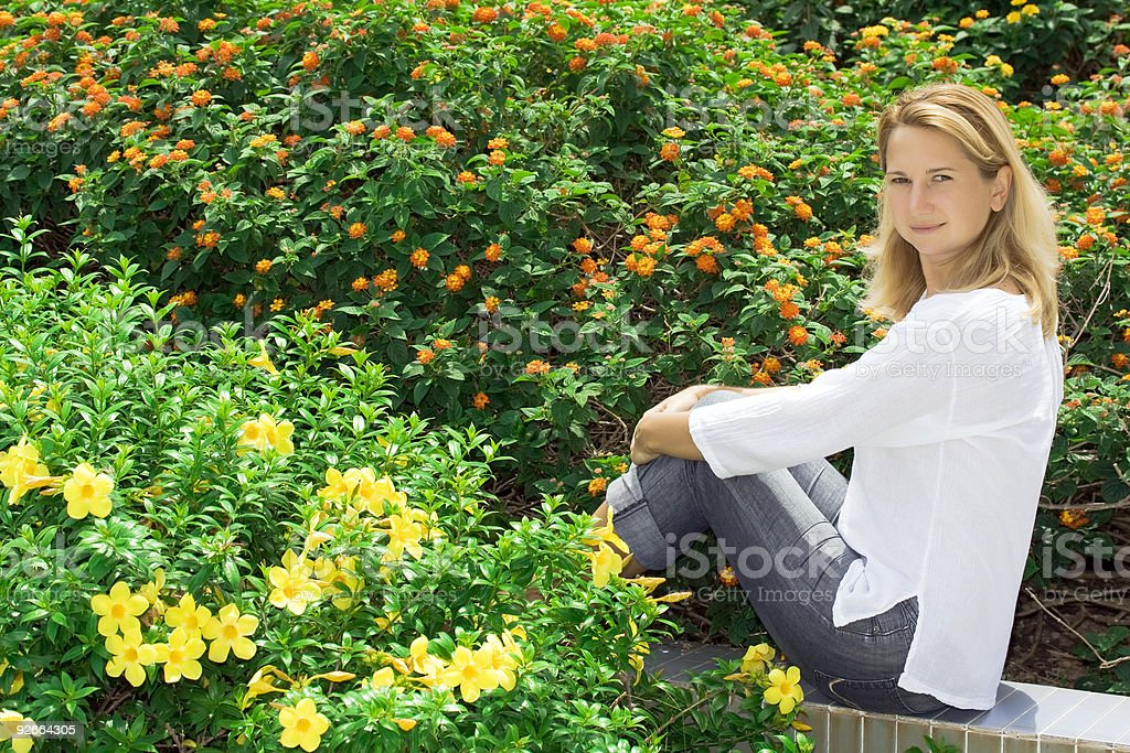 Young woman sitting in flowers royalty-free stock photo