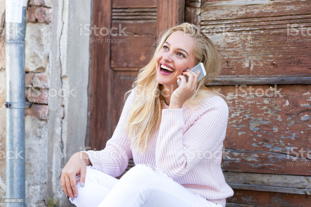Young woman sitting in front of door and using phone zbiór zdjęć royalty-free