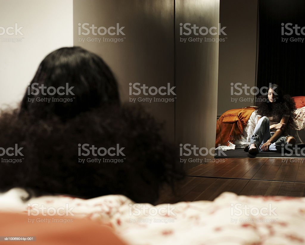 Young woman sitting in front of mirror in bedroom royalty free stockfoto