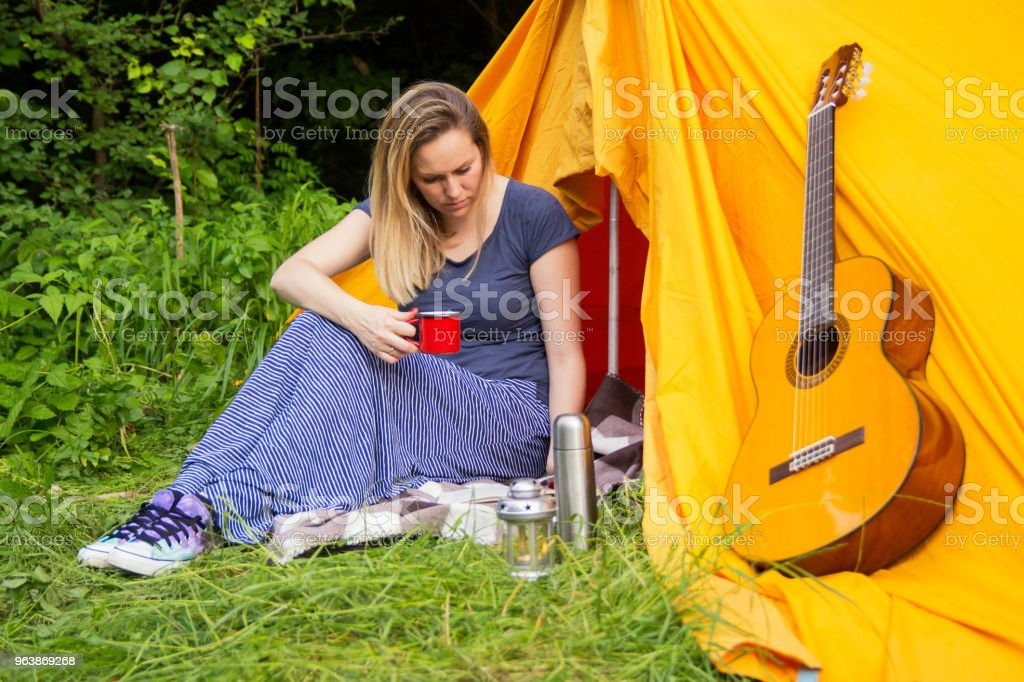 Young woman sitting in front of the tent - Royalty-free Adult Stock Photo