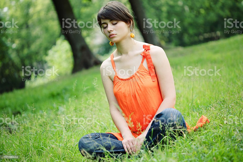 Young Woman Sitting in Grass and Closing Eyes royalty-free stock photo