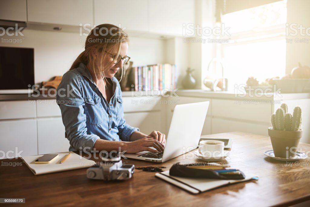 Young woman sitting in her kitchen working on a laptop stock photo