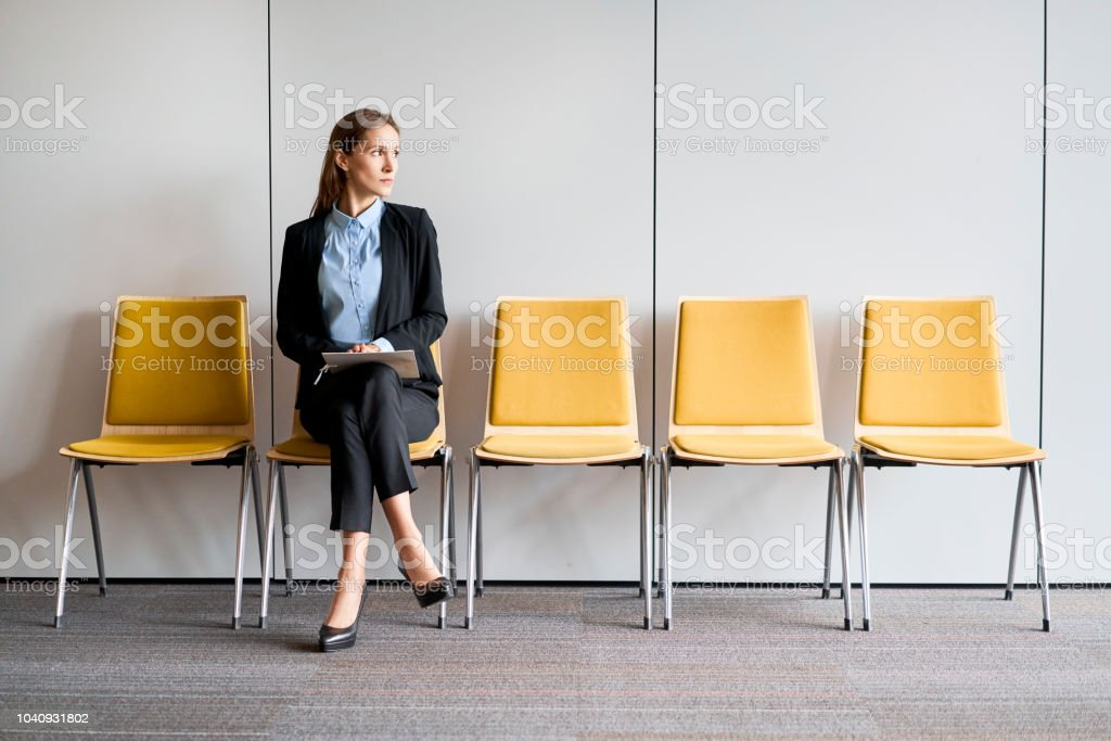 Young woman sitting in lobby with resume in hands and waiting for job interview stock photo