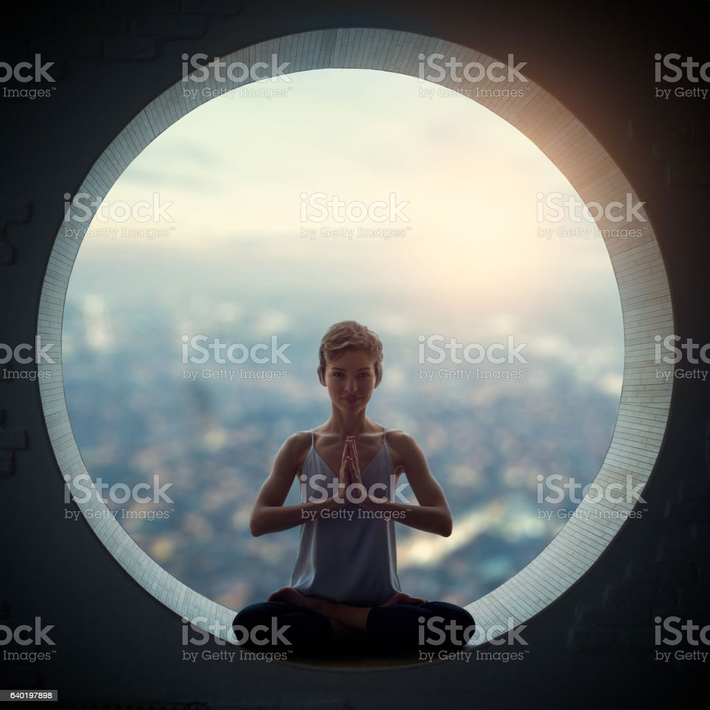 young woman sitting in lotus posture stock photo