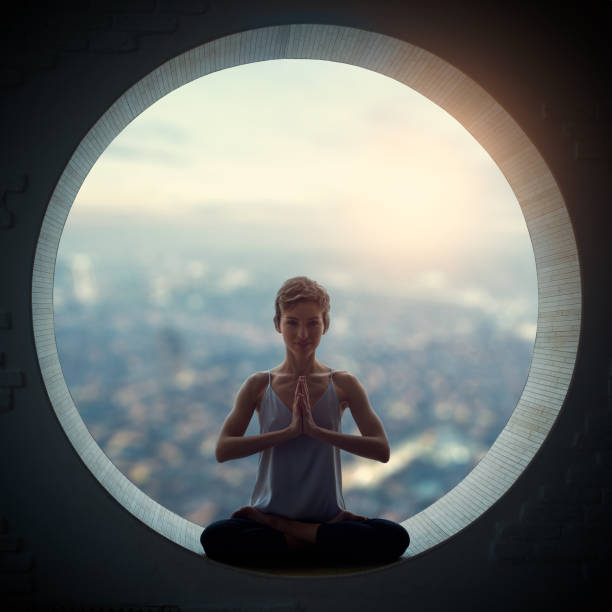 young woman sitting in lotus posture young woman doing yoga in the round window prayer pose yoga stock pictures, royalty-free photos & images