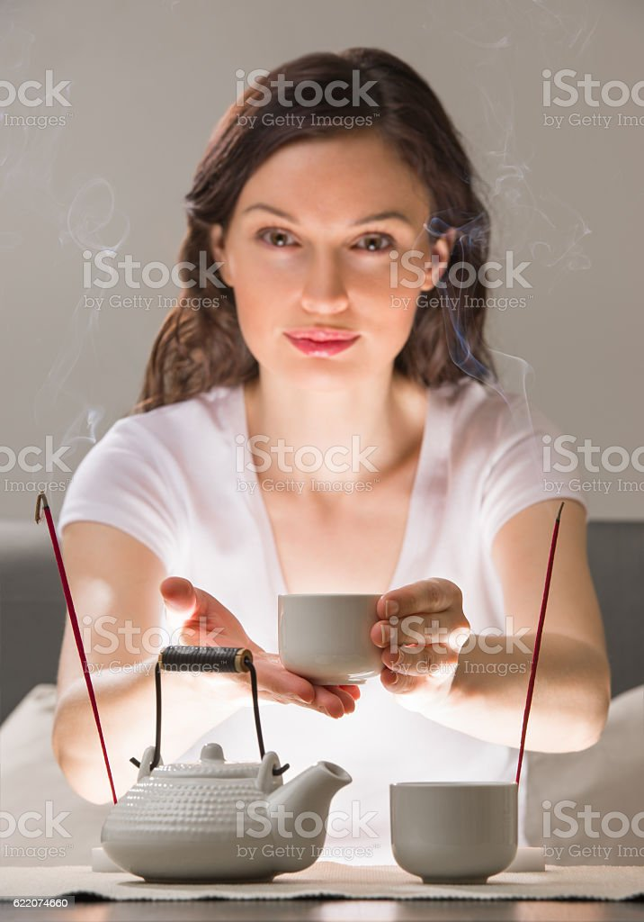 Young woman sitting in meditation pose in front of tea stock photo