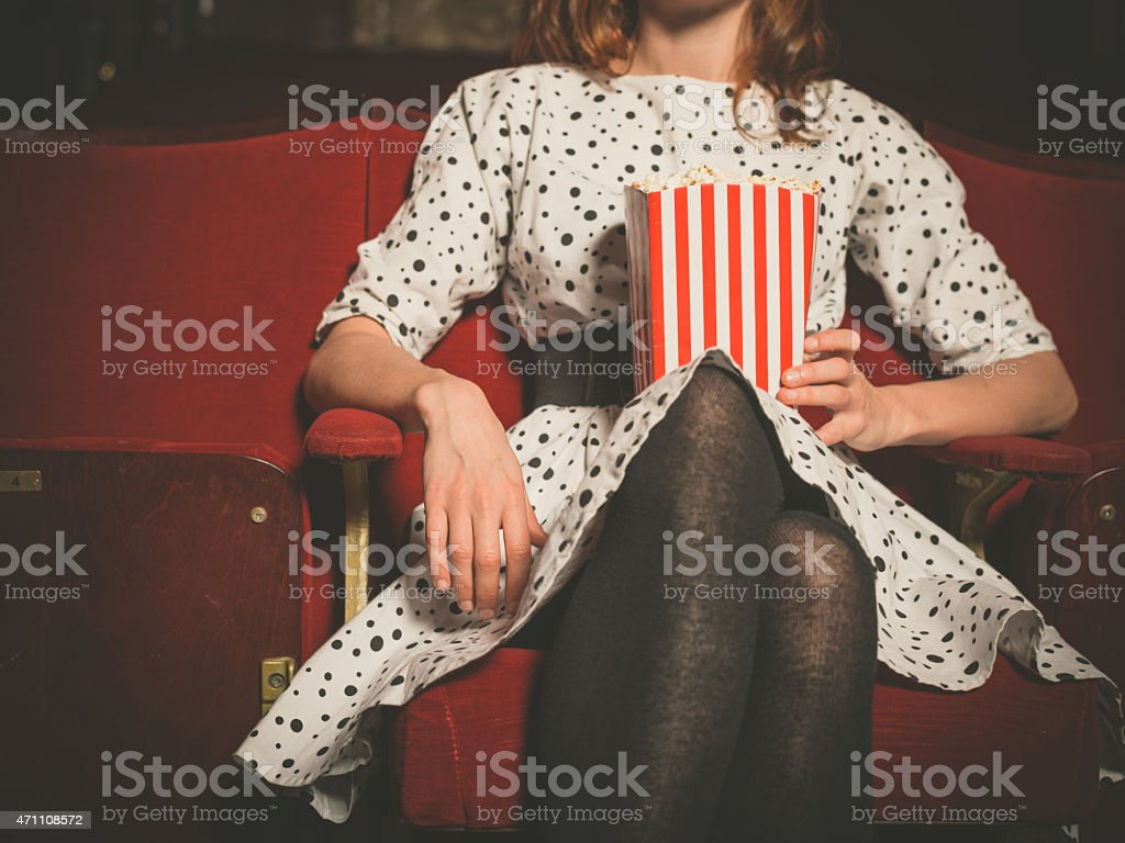 Young woman sitting in movie theater with popcorn stock photo