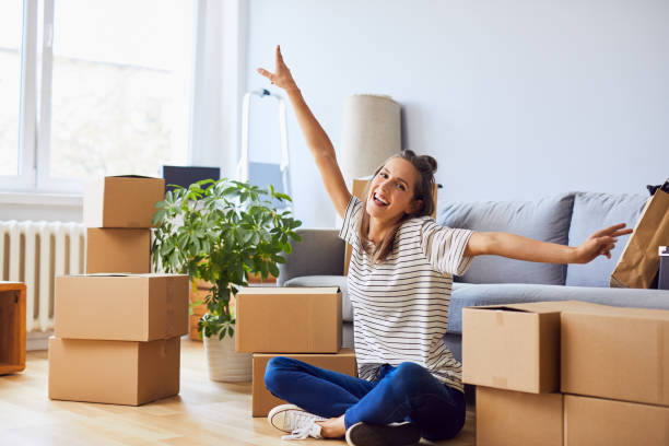 Young woman sitting in new apartment and raising arms in joy after moving in stock photo