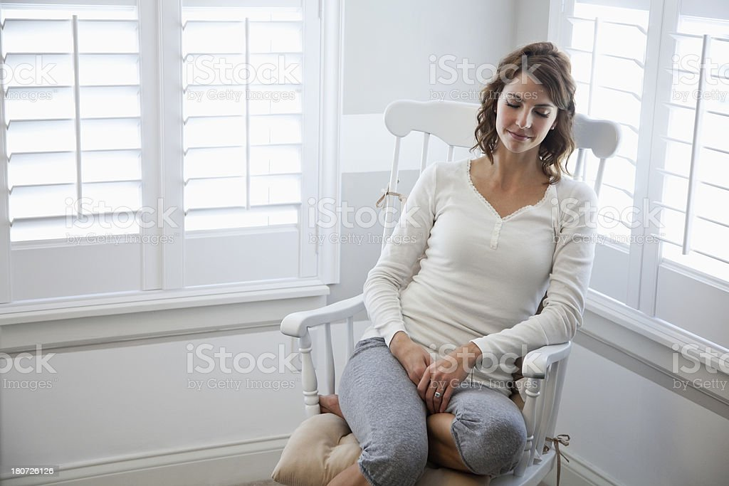 Young woman sitting in rocking chair stock photo
