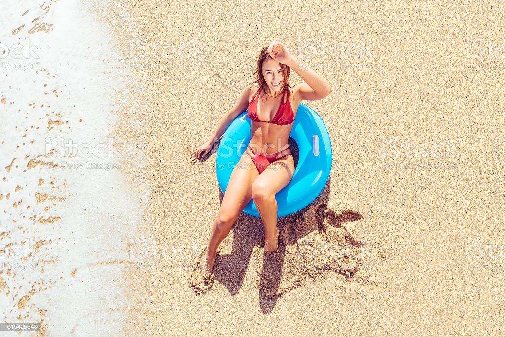 Young Woman sitting in rubber ring at the Beach. stock photo