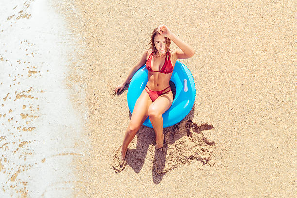 young woman sitting in rubber ring at the beach. - rubber ring stock photos and pictures