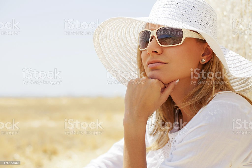 Young woman sitting in the field, wearing sunhat and sunglasses stock photo