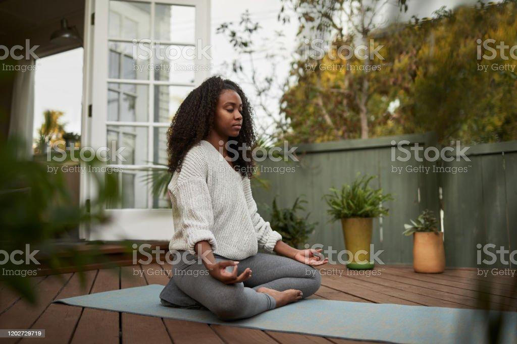 De jonge vrouwenzitting in de lotusstelt buiten op haar terras - Royalty-free 20-29 jaar Stockfoto