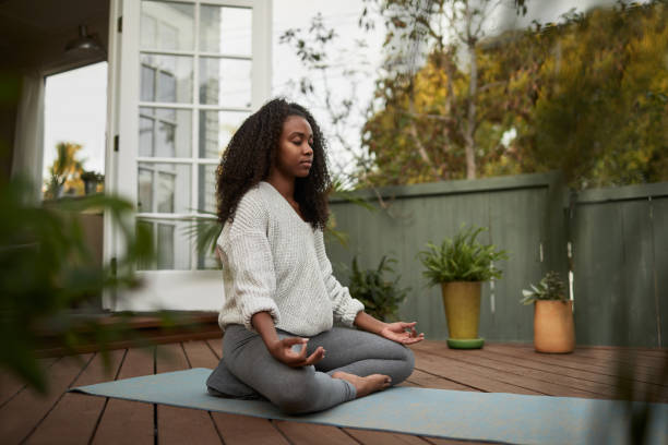 Young woman sitting in the lotus pose outside on her patio Young African American woman sitting on exercise mat outside on her patio and meditating in the lotus pose during a yoga session wellbeing stock pictures, royalty-free photos & images
