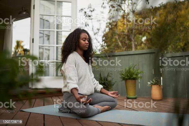 De Jonge Vrouwenzitting In De Lotusstelt Buiten Op Haar Terras Stockfoto en meer beelden van 20-29 jaar
