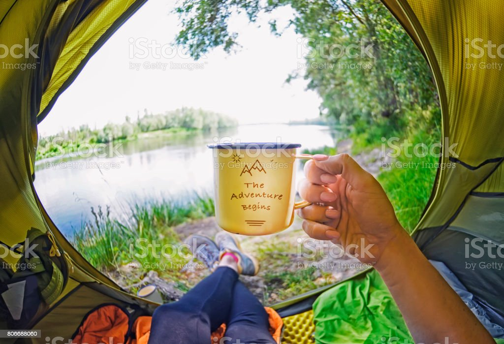 Young woman sitting   in the tent and drinking tea while looking on the Desna river stock photo