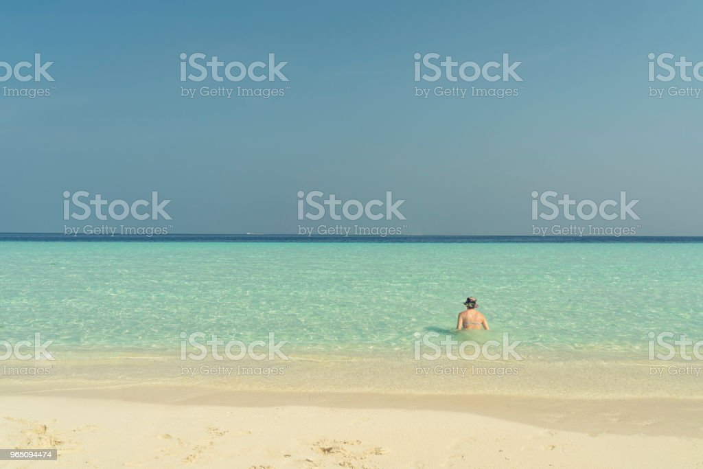 Young Woman sitting in the turquois sea royalty-free stock photo