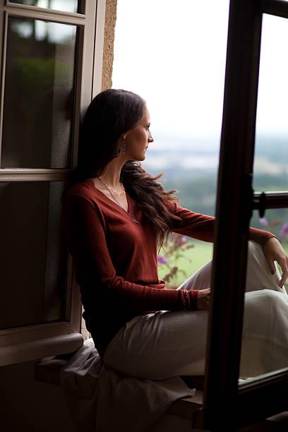 ウィンドウに座る若い女性 ストックフォト