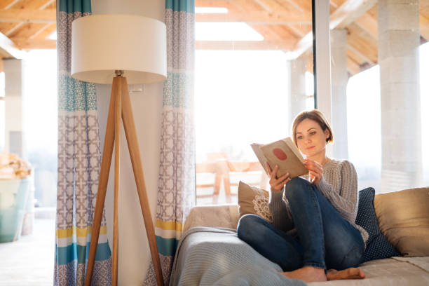 A young woman sitting indoors on a sofa at home, reading a book. stock photo