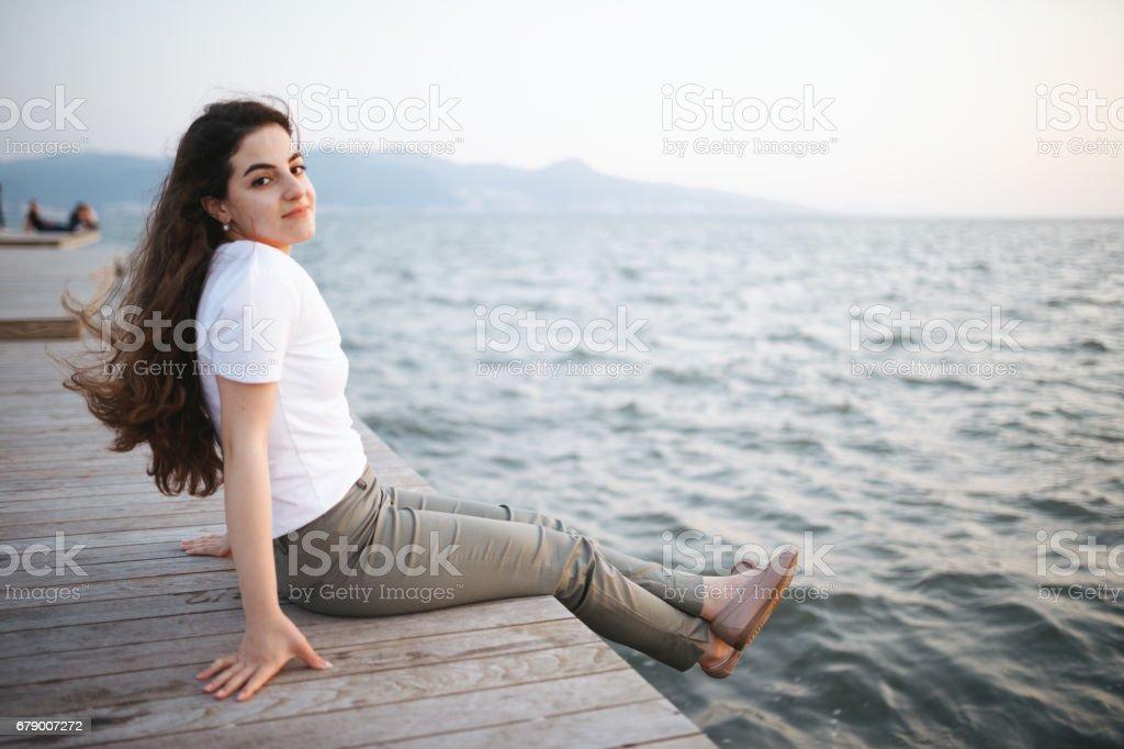 Genç kadın oturma seyir günbatımı royalty-free stock photo