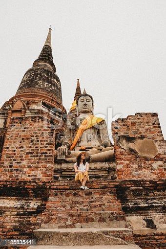 Young woman sitting near a Buddha statue in Ayutthaya, Thailand