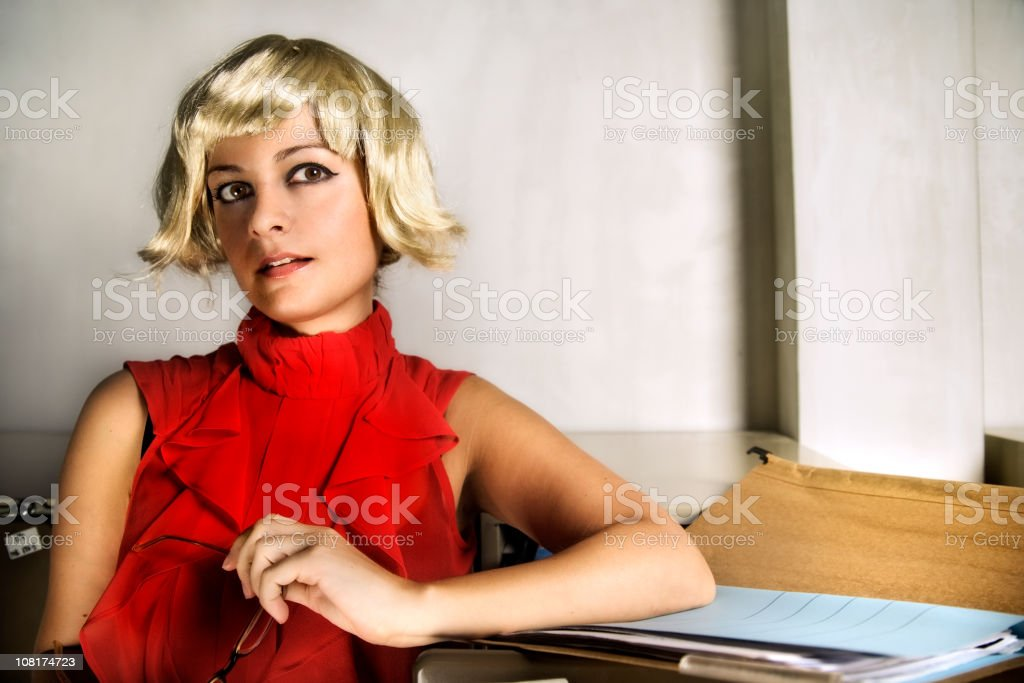 Young Woman Sitting Near File Folder Wearing Wig royalty-free stock photo