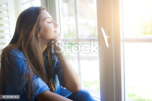 909062786 istock photo Young woman sitting next to the window at home 623095302