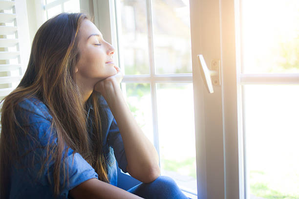 Young woman sitting next to the window at home Smiling young woman sitting next to the window, eyes closed. With long hair, wears denim shirt. Hand on chin. Focus on foreground. eyes closed woman stock pictures, royalty-free photos & images