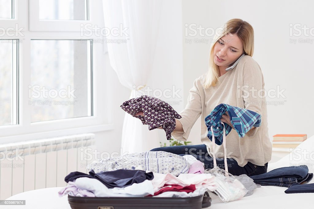 Young woman sitting on a bed and packing a suitcase stock photo