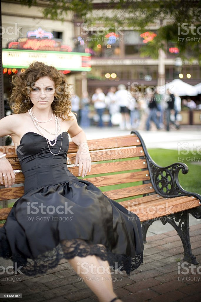 young woman sitting on a bench dowtown black dress stock photo