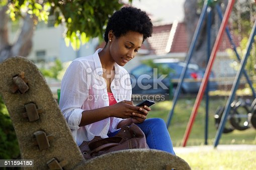 istock Young woman sitting on a bench sending text message 511594180