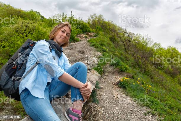 Photo of A young Woman sitting on a mountain stone path and posing for the camera. Sky with clouds on the background. Bottom view