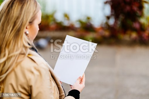 Young woman sitting on a park bench reading a magazine with a blank cover page. Magazine as mock-up.