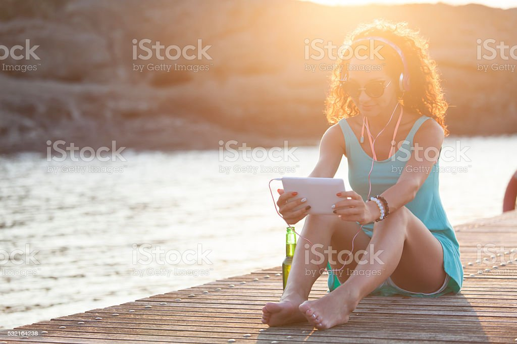 Young woman sitting on a pier and listening music stock photo