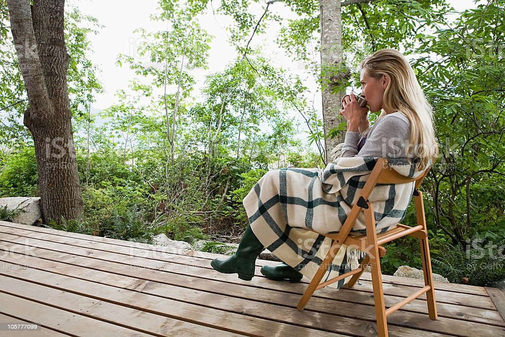 Young woman sitting on a porch royalty-free stock photo