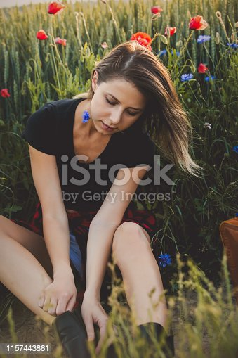 Young woman sitting on a roadside of countryside road with suitcase