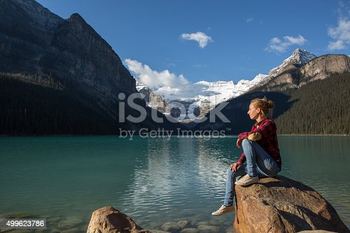 Young woman sitting on a rock by the lake relaxing and enjoying the spectacular landscape.