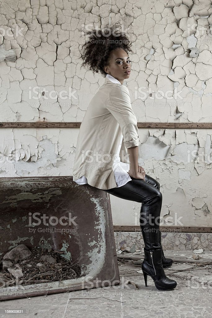 Young woman sitting on a rusty bath. royalty-free stock photo