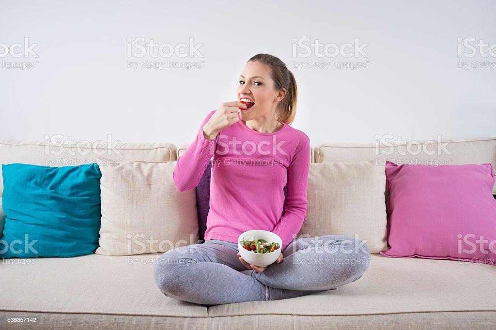 若い女性に座っているソファーとヘルシーなサラダを食べています。 ストックフォト