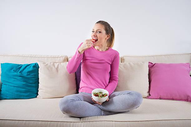 若い女性に座っているソファーとヘルシーなサラダを食べています。 - ローフード ストックフォトと画像