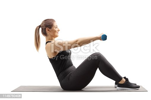 istock Young woman sitting on an exercising mat and working out with dumbbells 1149750408
