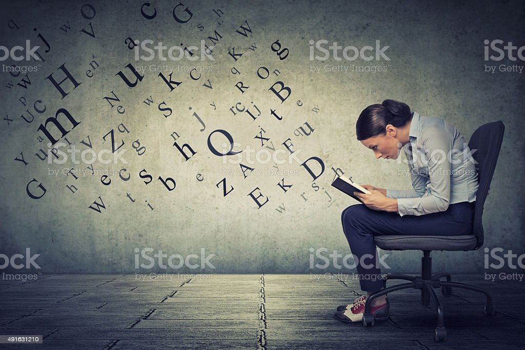 Young woman sitting on armchair and reading stock photo