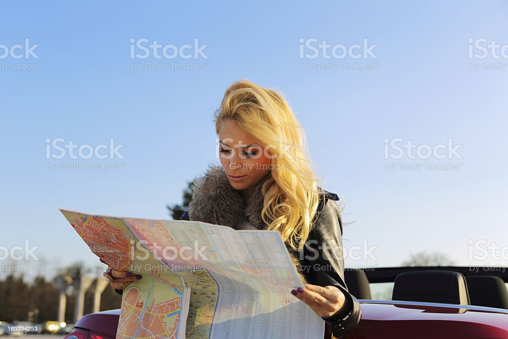 Young woman sitting on back of car,looking at map stock photo