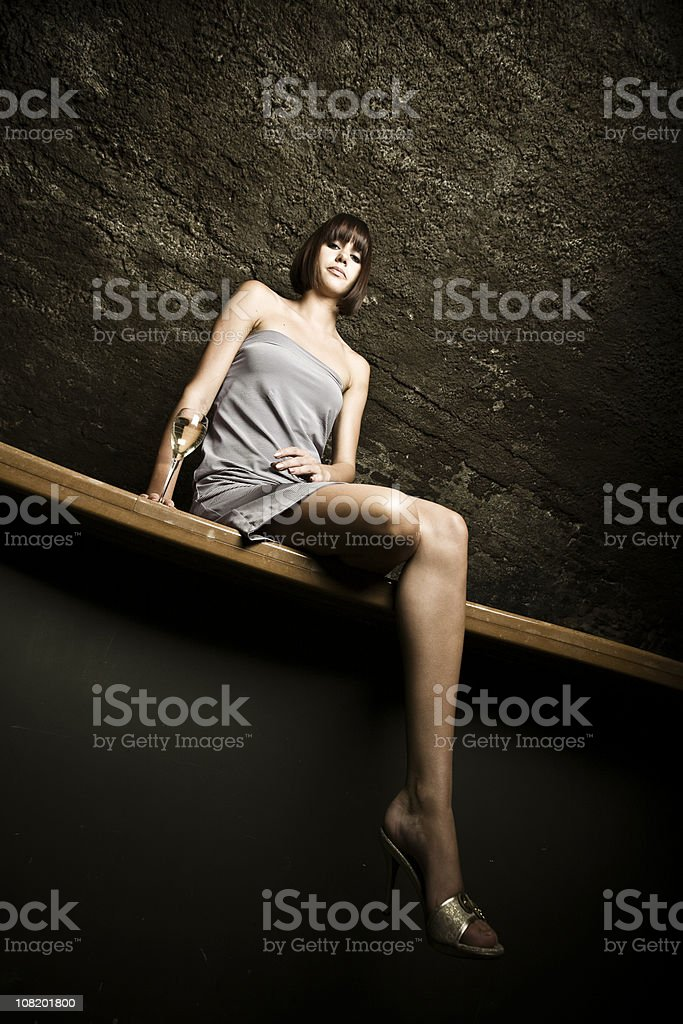 Young Woman Sitting on Bar Against Wall Drinking Champagne royalty-free stock photo
