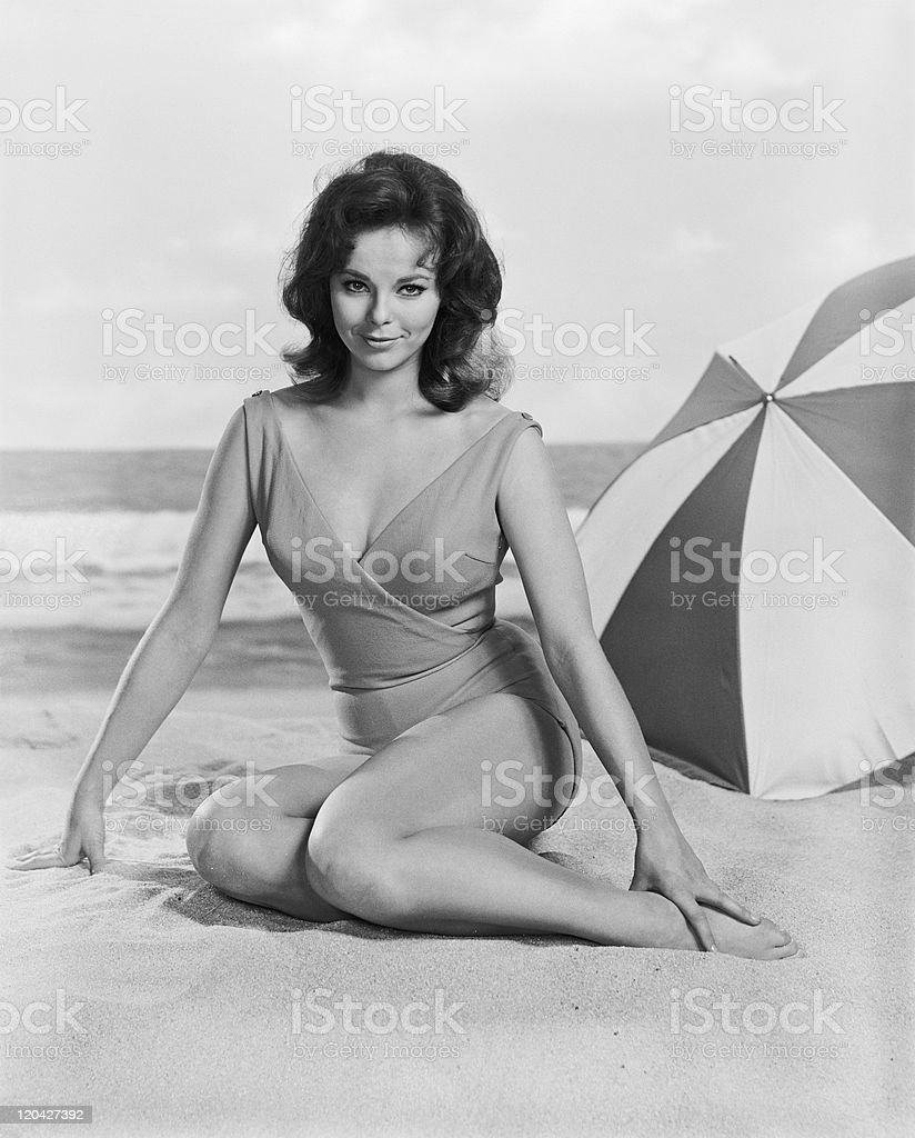 Young woman sitting on beach, smiling, portrait stock photo