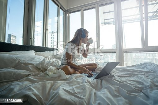 Young woman sitting on bed and using laptop