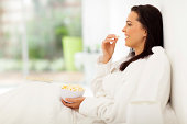 istock young woman sitting on bed eating popcorn and watching tv 479027415