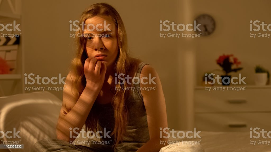 Young woman sitting on bed, suffering panic attack and feeling...