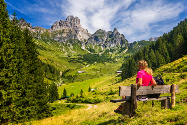 Young woman sitting on bench and enjoys view on big Bischofsmütze, Dachstein mountains, alps stock photo
